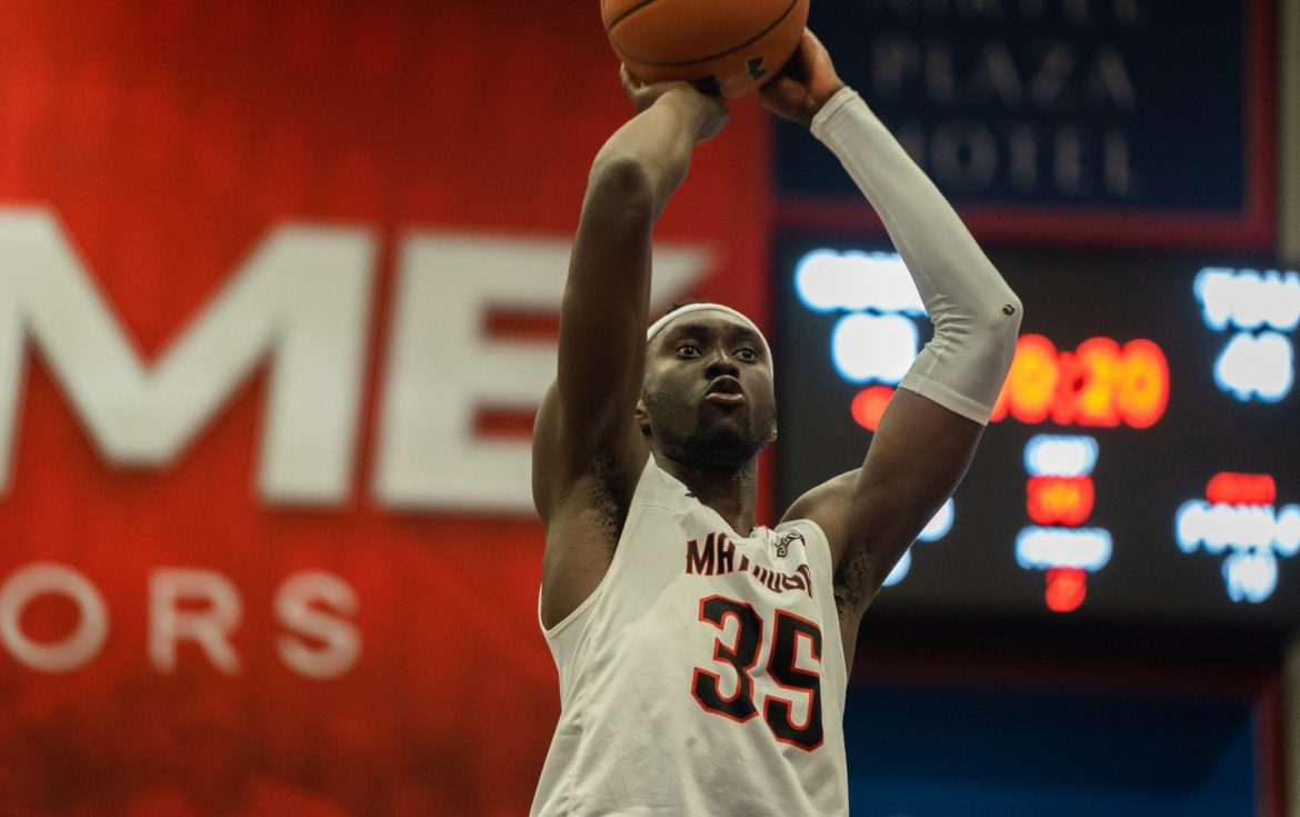 A CSUN Men's basketball player making jump shot in the white jersey