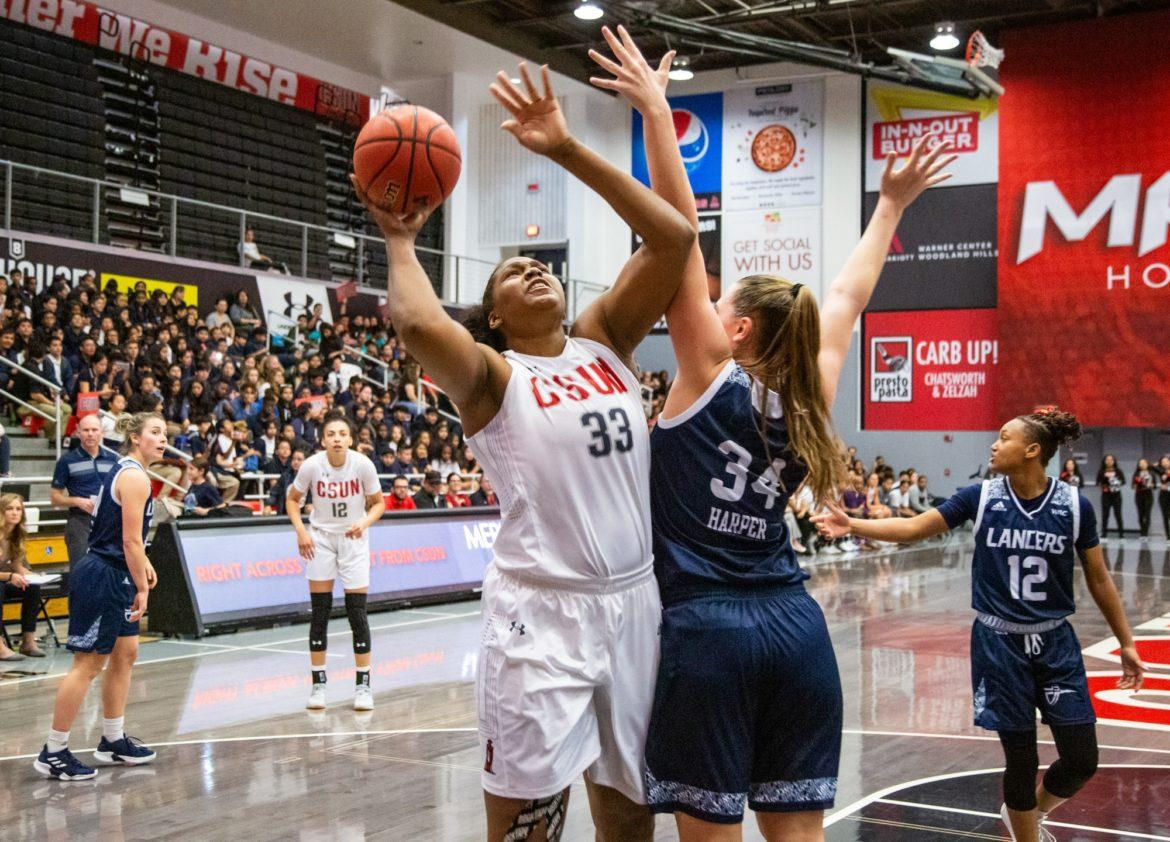 A CSUN women's basketball player jumps in the air with a ball trying to score.