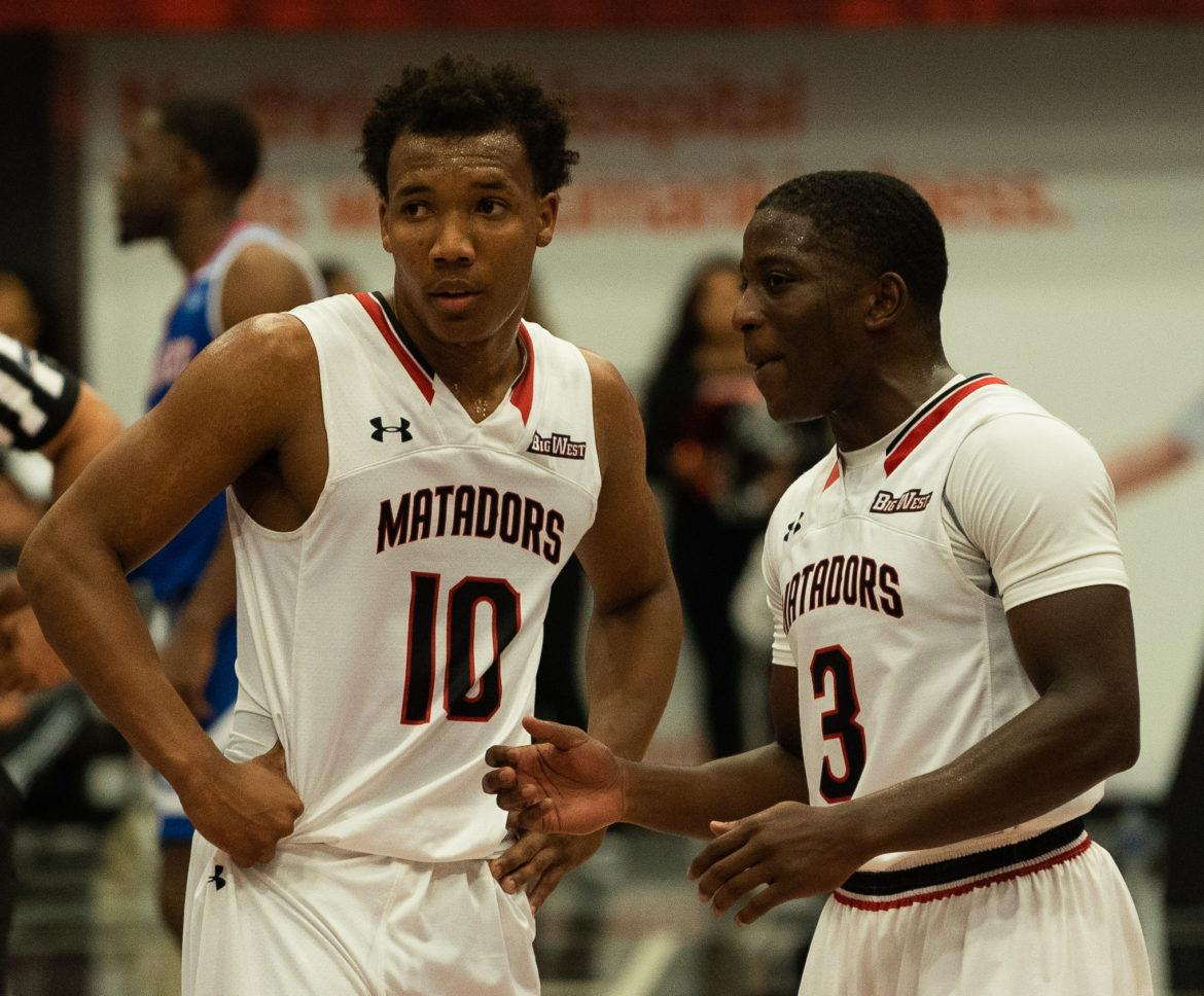 Two CSUN Mens basketball players communicating with each other in white CSUN jerseys