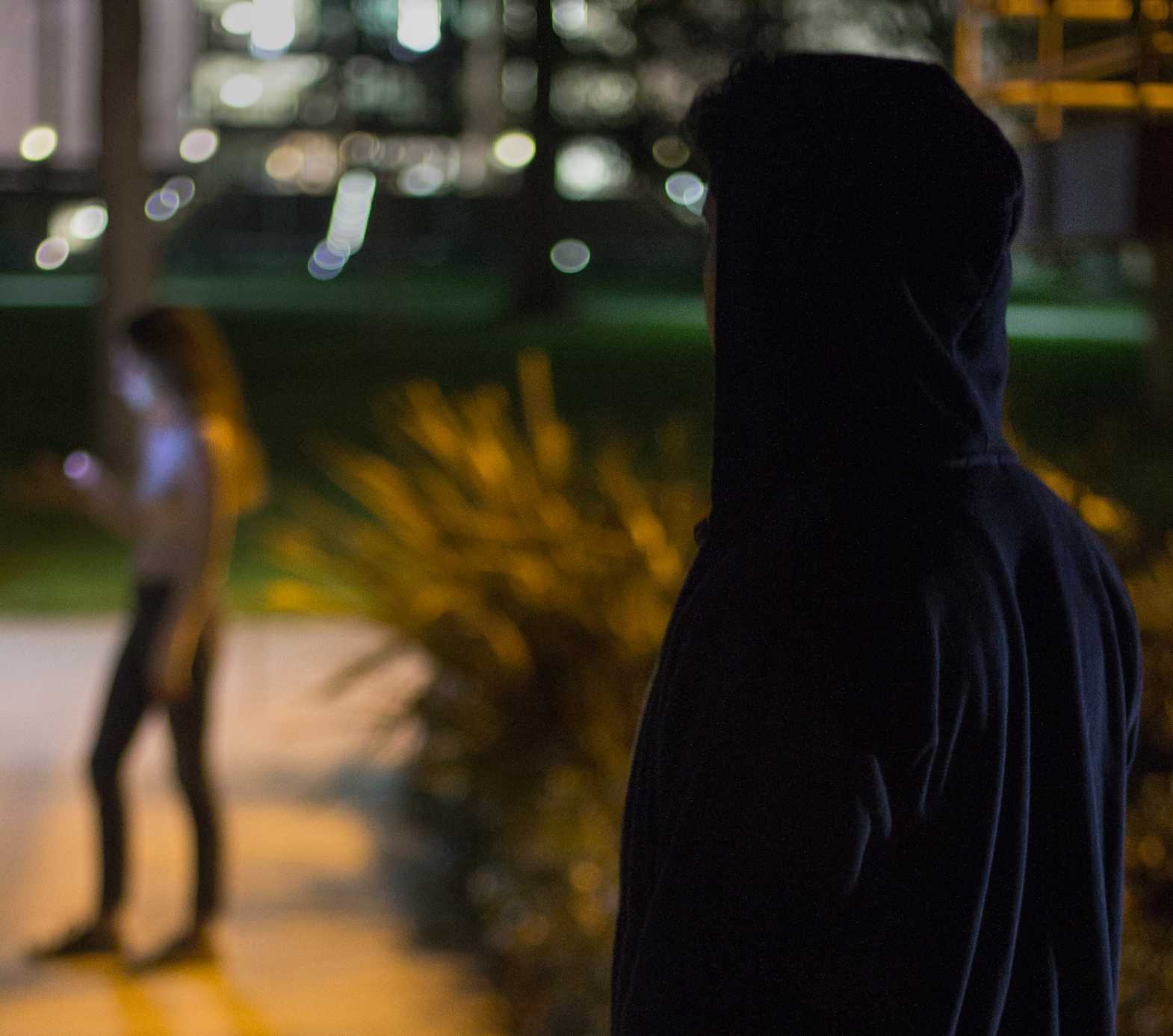 A CSUN student in a dark blue jacket standing on a walk-way on CSUN campus.