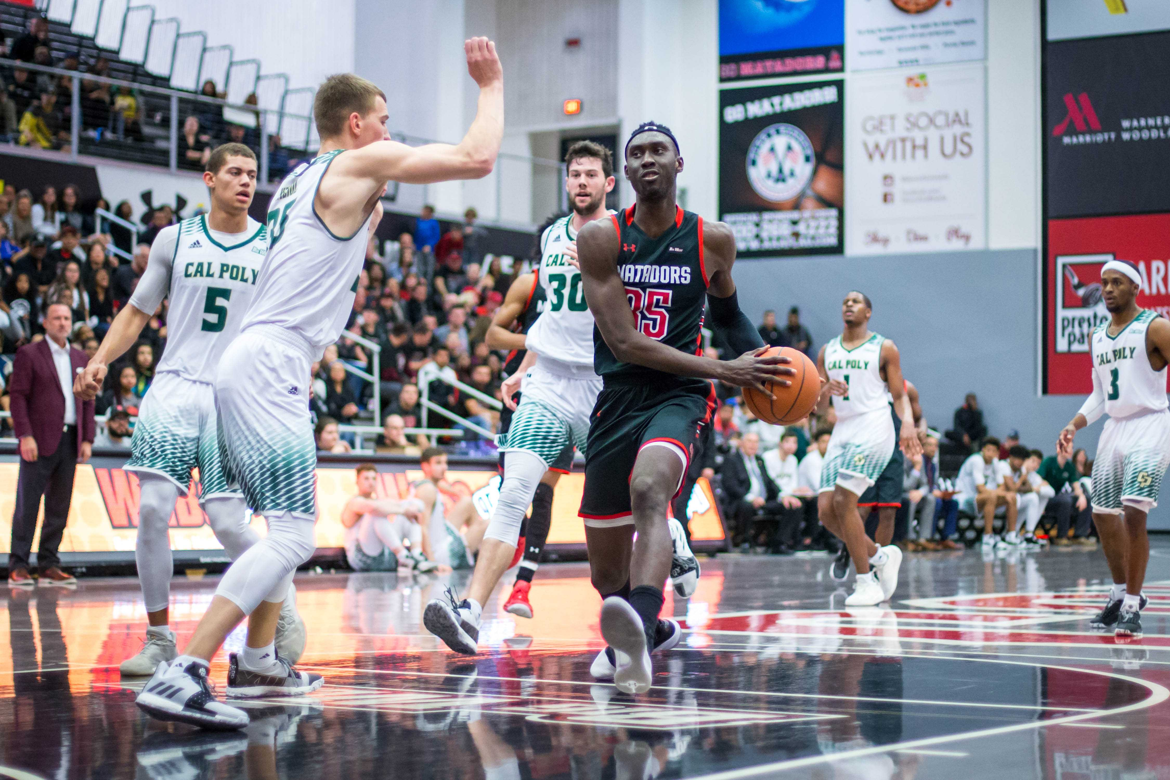 A CSUN Men's basketball player in black jersey trying to go around a defender tp the basket.