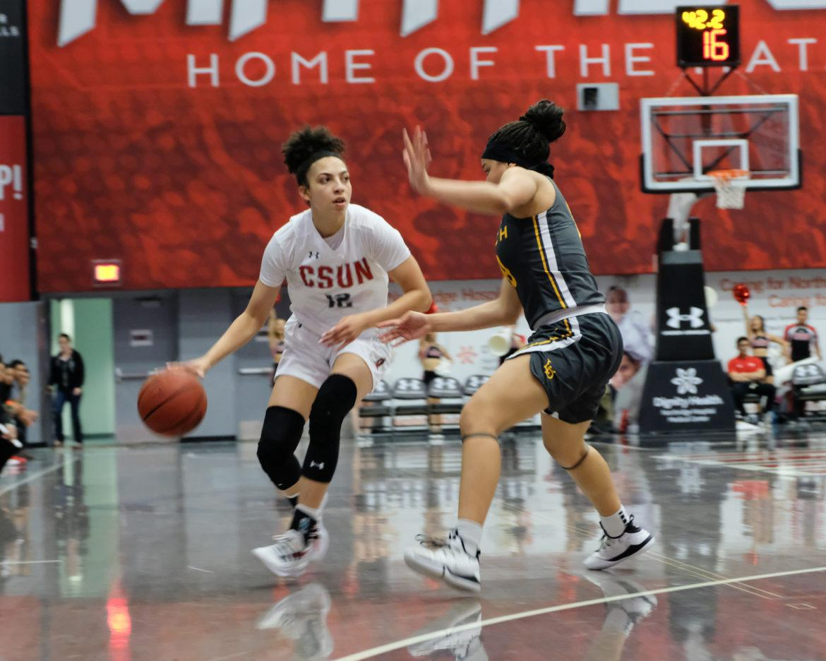 A CSUN Women's basketball player in white jersey attempts to drive past her defender