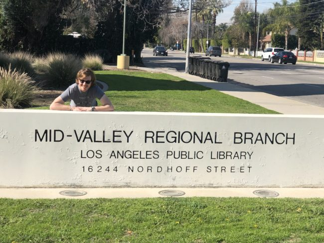A student taking photo in front of the LA public library