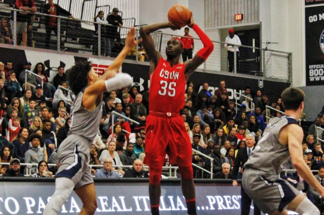 A CSUN Men's basketball player making jumpshot in front of a defender
