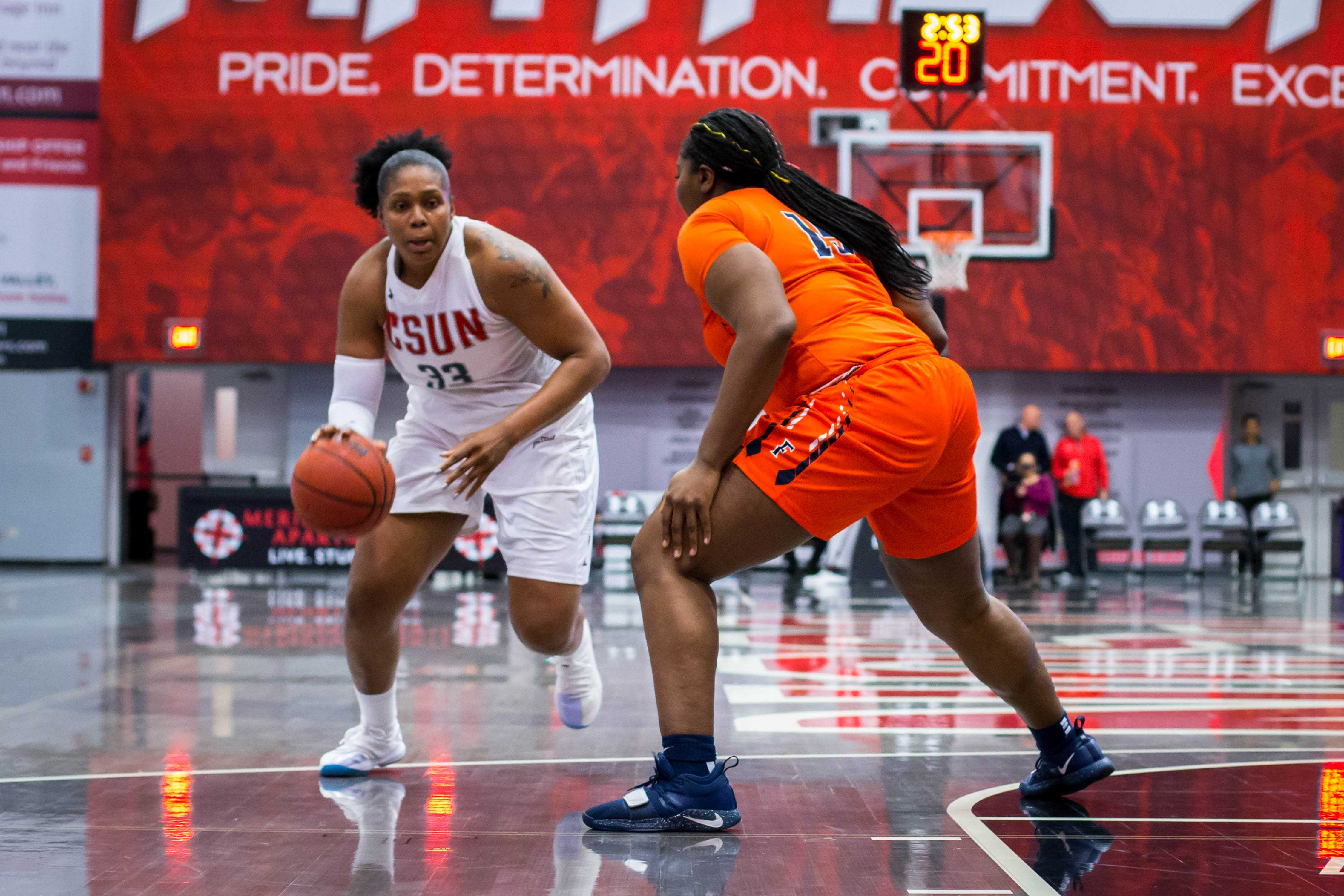 A CSUN Women's basketball play in wihte jersey handing the ball to get pass a denfender in orange jersey.