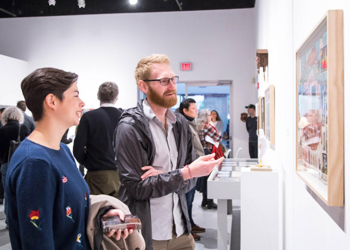 Two students discussing about an artpiece in an expo