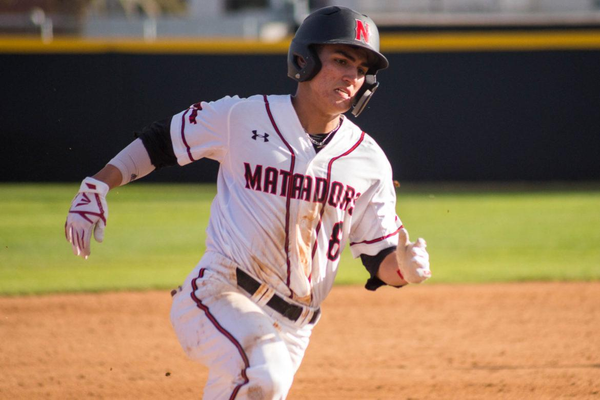 A+CSUN+men%27s+Baseball+player+in+white+jersey+running+between+different+bases