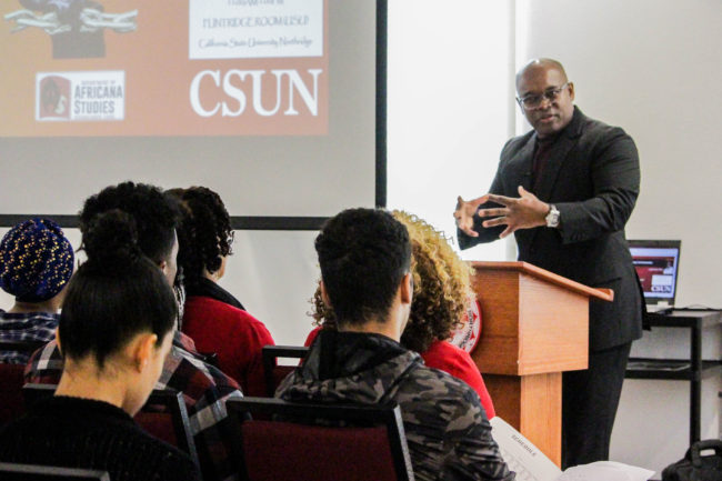 An African American professor giving lecture to his students.