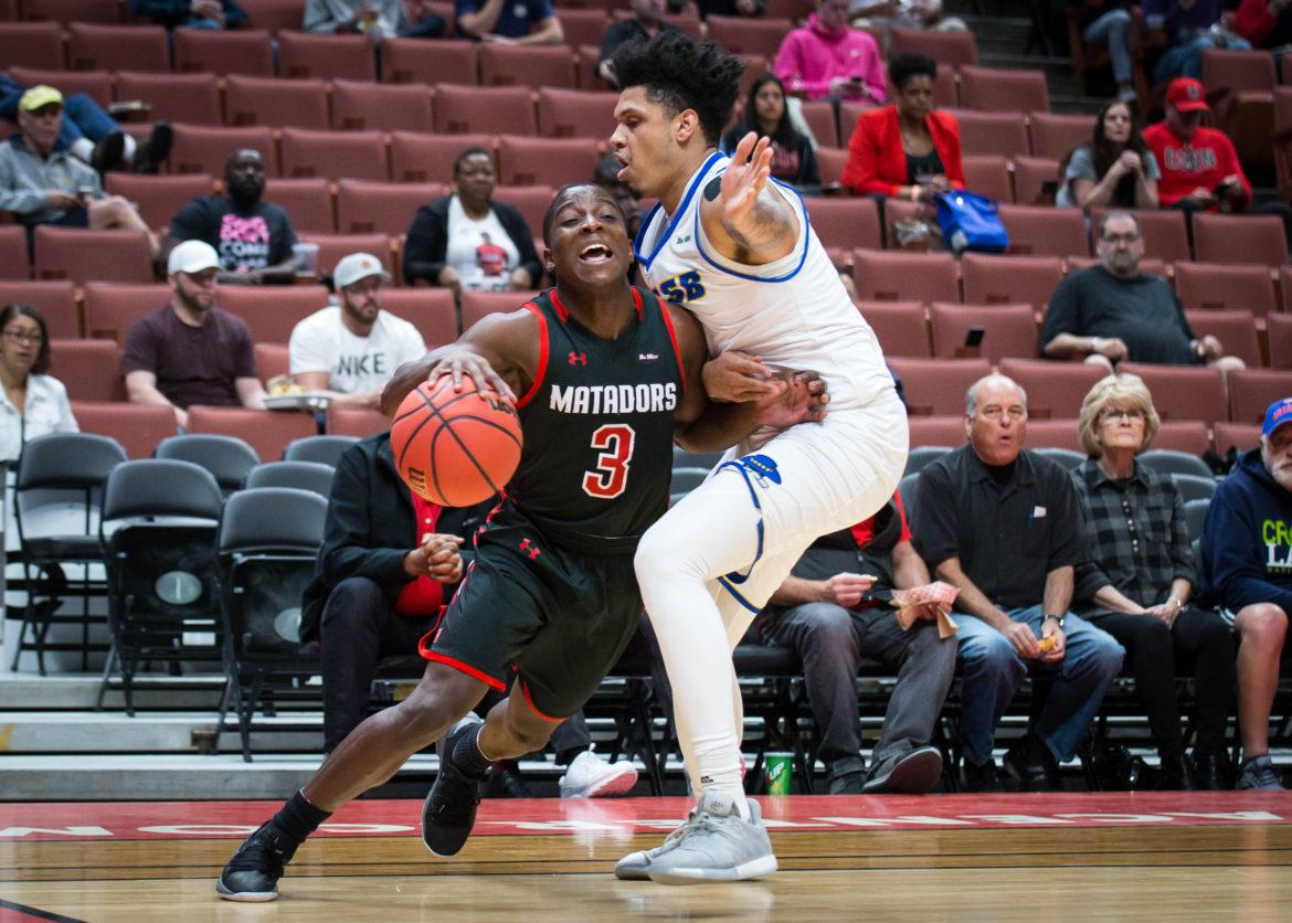 A CSUn Men's Basketball player in black jersey attempts to frive pass the defender