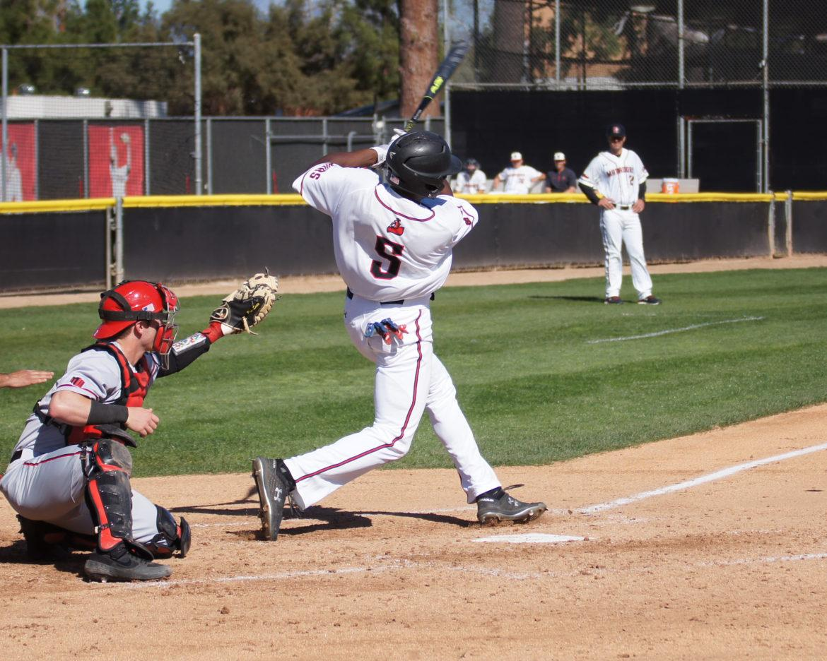 A CSUn Men's Baseball player in white jersey hiting a ball in a game.