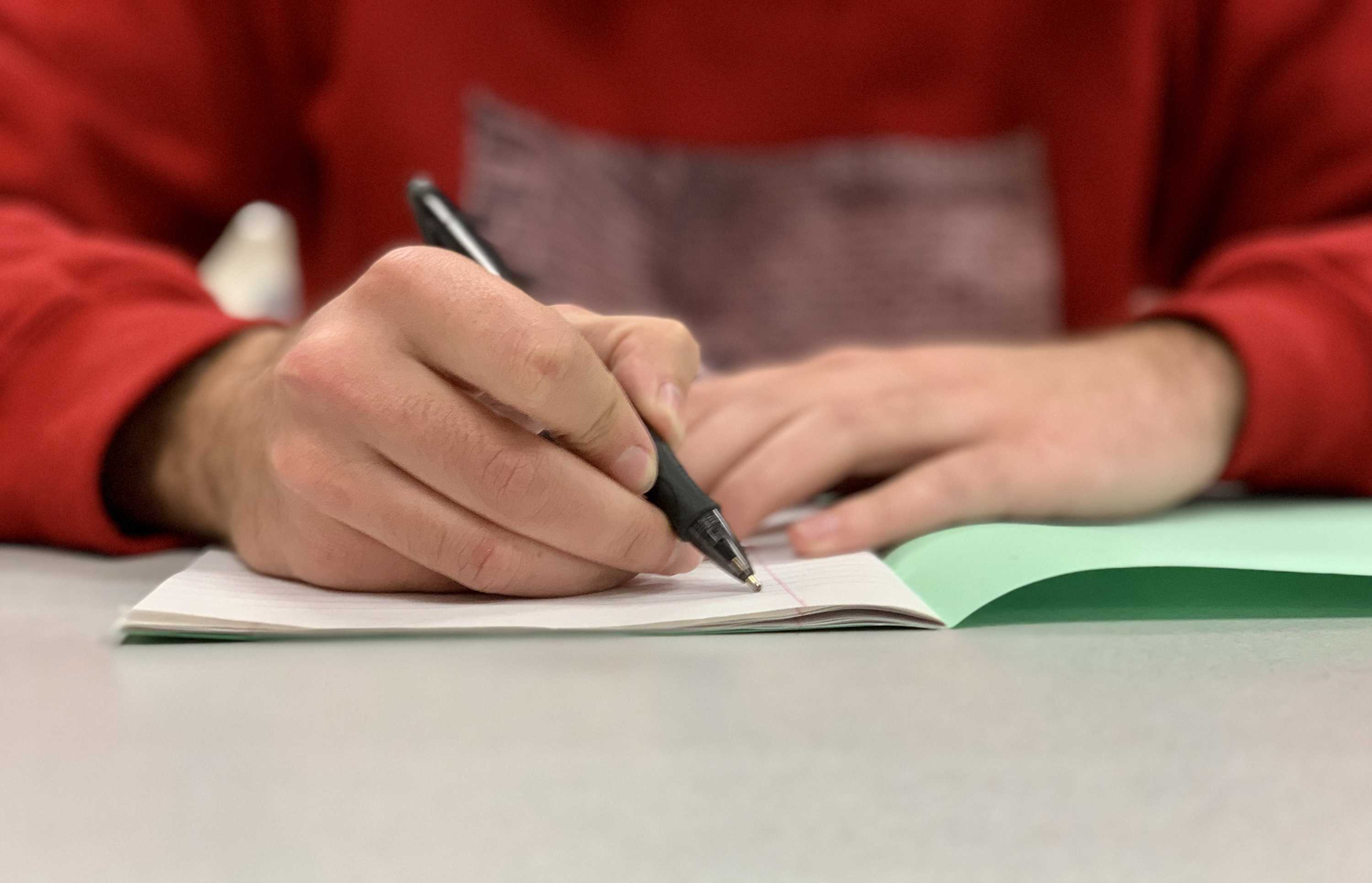 A picture illustation of a student trying to write something on a green book