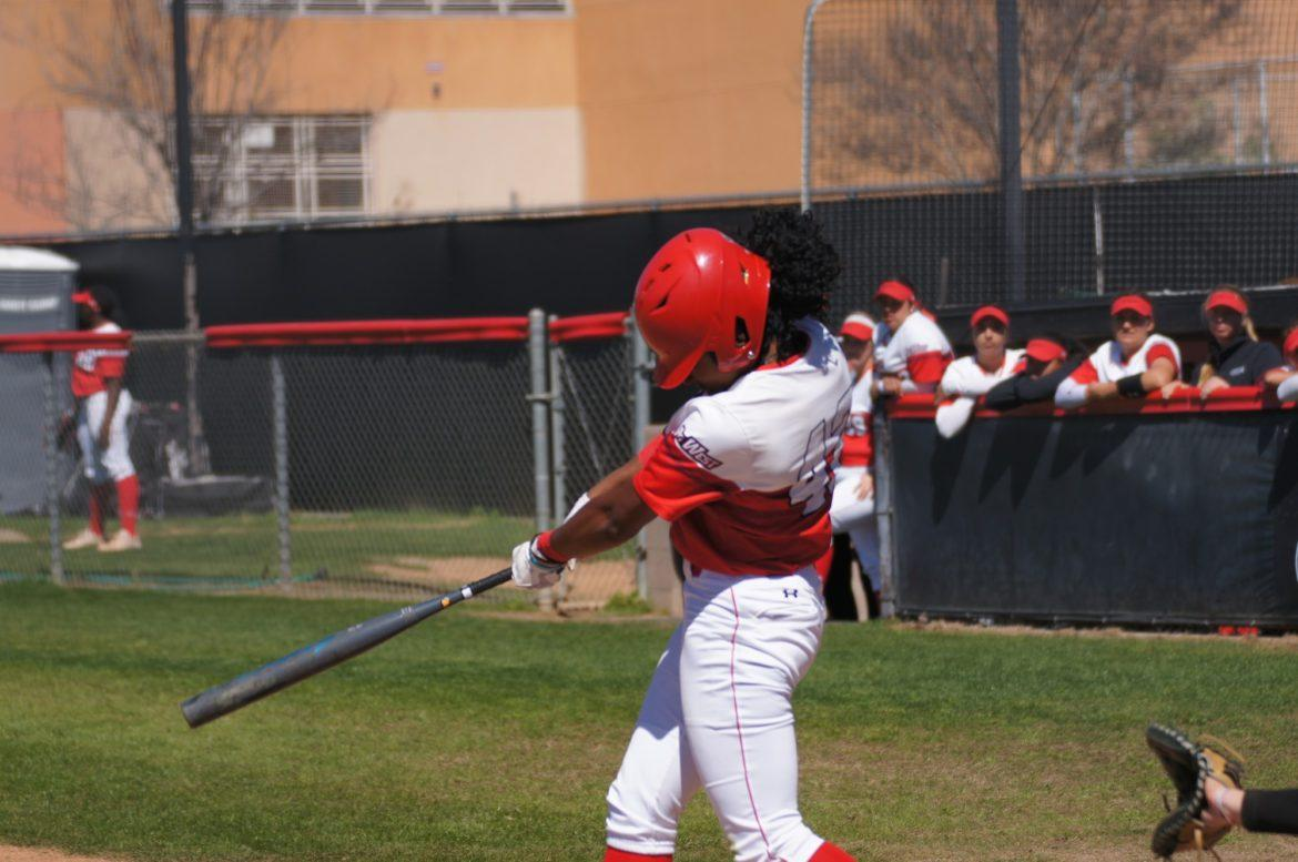 A CSUN Women's Softball player trying to hit the ball