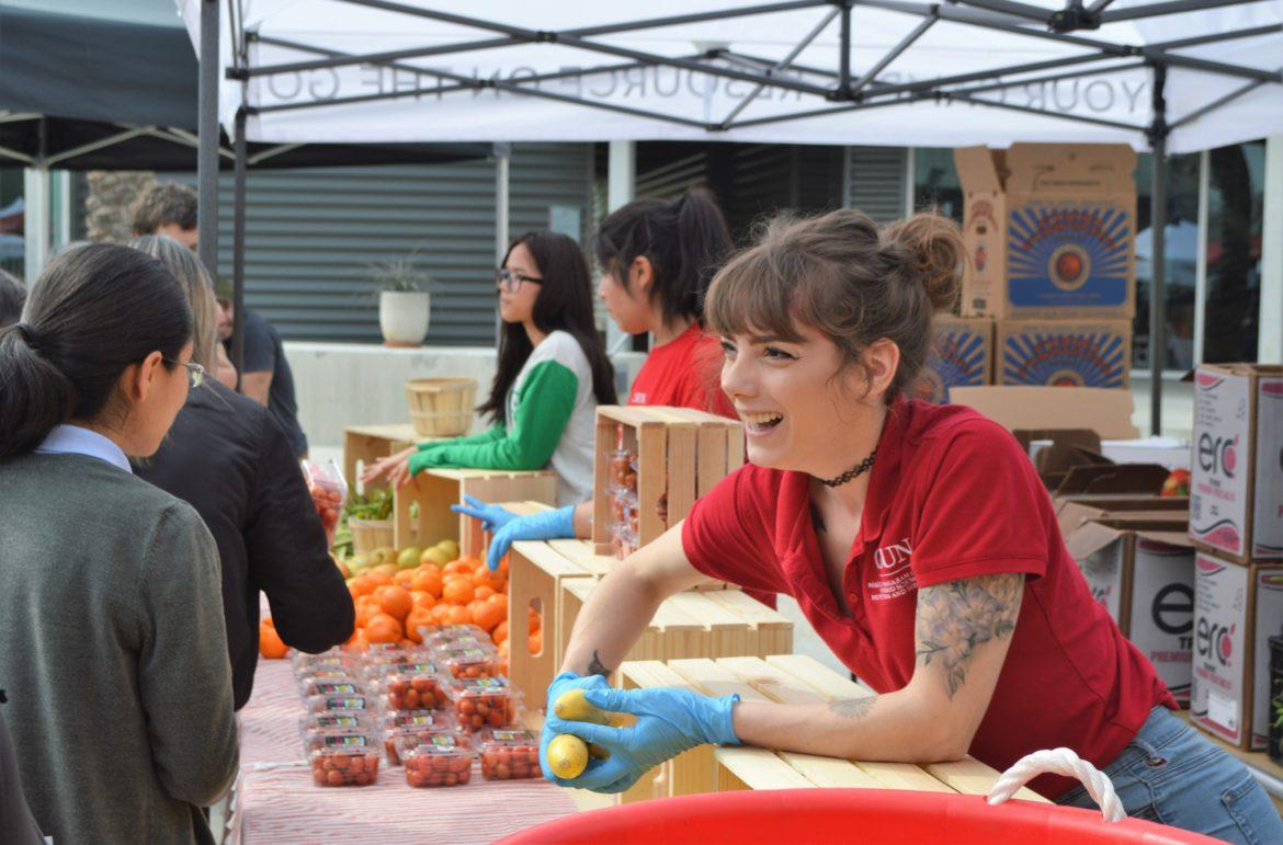 A CSUn Female student handing out fruit at the University Palace