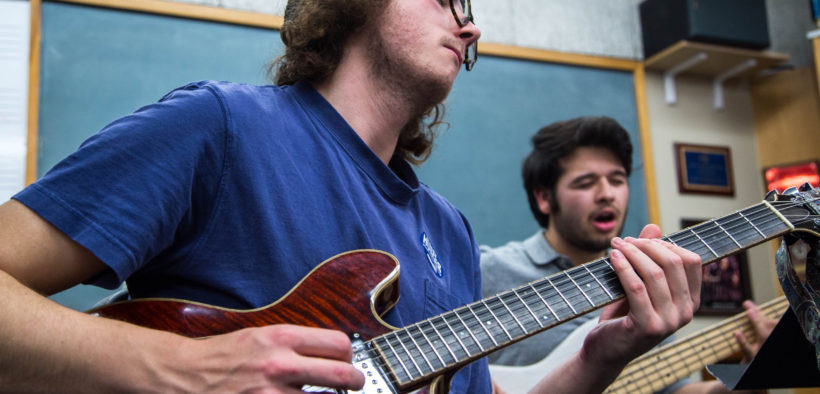 A music major student playing guitar in class