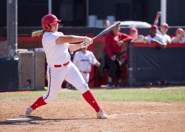 A CSUN Softball Player in white jersey swing a bat to score