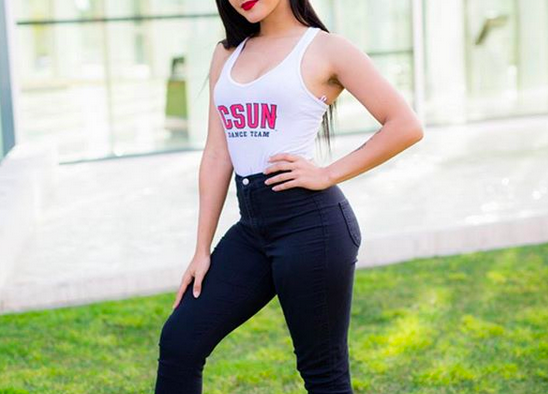 A Female CSUn student in white dancing team jersey