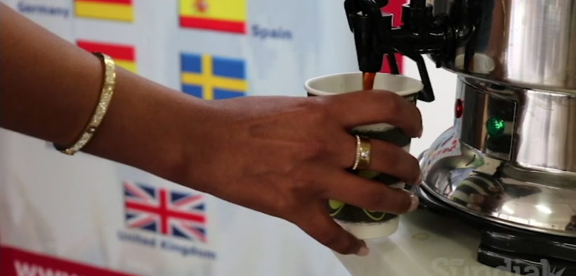 A person pouring coffee in a cup during an event
