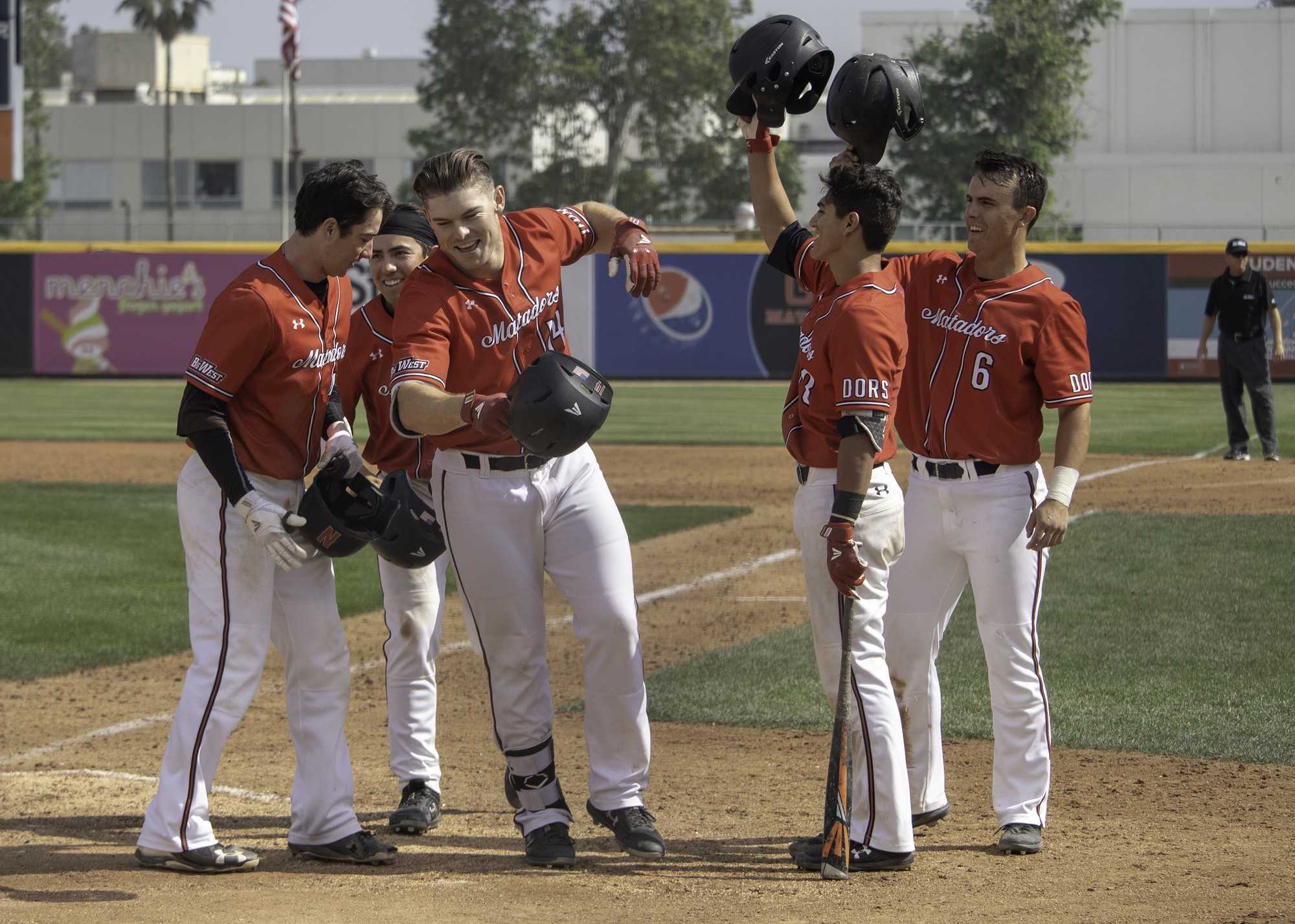 Junior Blake Doremus (center) is congratulated by his teammates after hitting a grand slam to give his team the lead in the seventh inning of CSUN's 6-3 victory over Hawaii on Sunday. Doremus pinch hit for sophomore Victor Cerny and deposited a 1-1 pitch over the left field wall, winning the game and the series for the Matadors. Photo credit: Tyler Wainfeld