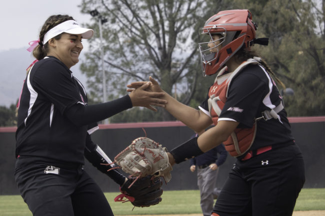 Two CSUN Softball players in black jersey giving each other high fives