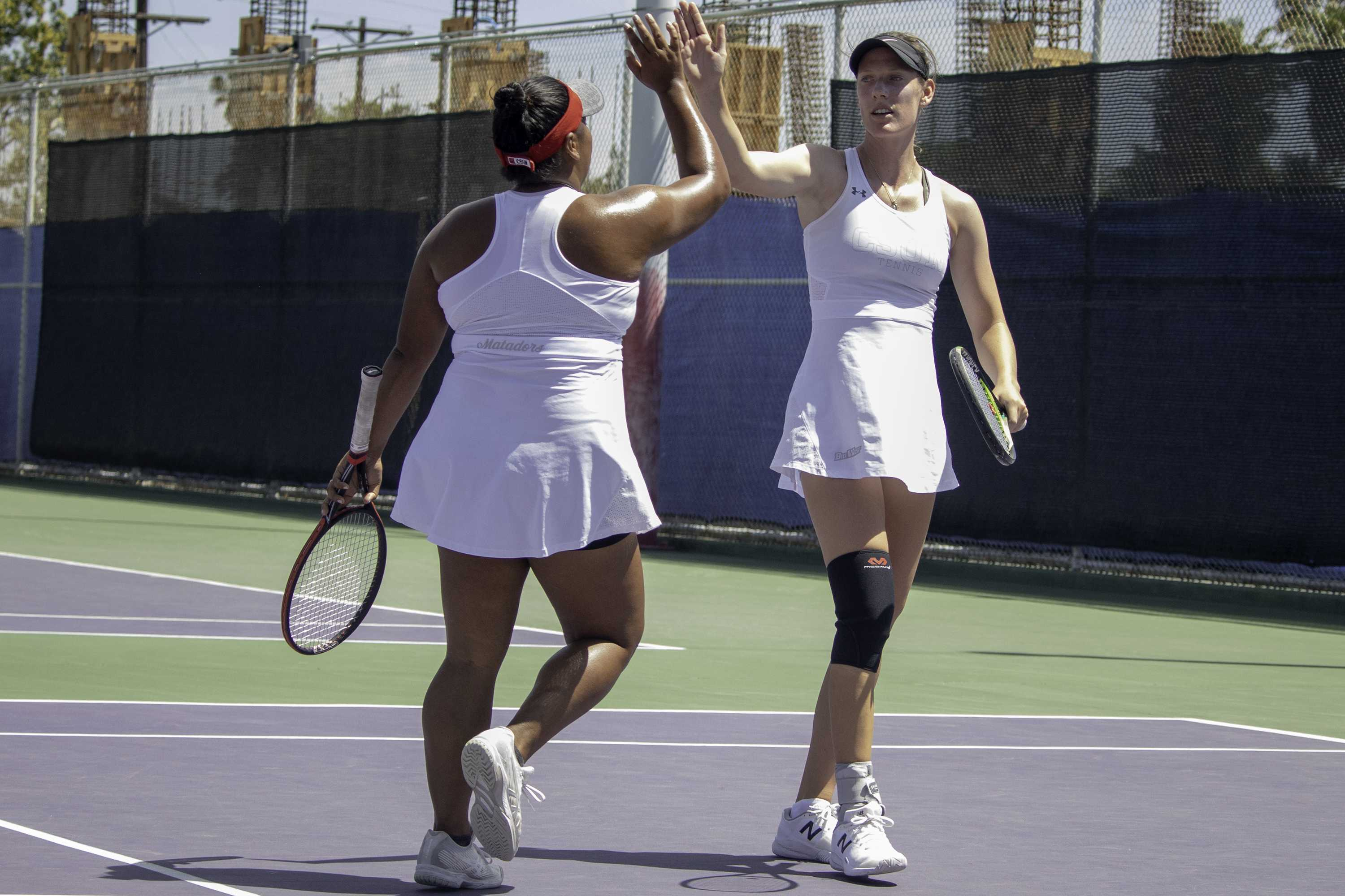 Seniors Monika Van de Vondel (right) and Skyla Alcon (left) high-five each other during their final home doubles match at CSUN against UC Santa Barbara on April 19. Their match was suspended after the Matadors lost the other two doubles matches before the pair lost both of their respective singles matches later in the day. Photo credit: Tyler Wainfeld