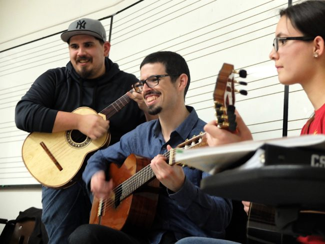 three students playing guitars