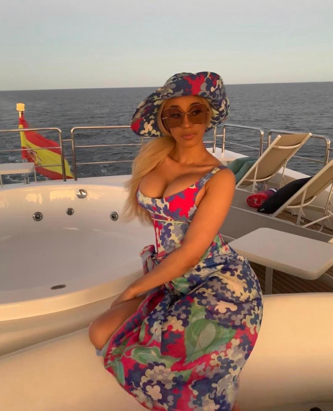a Latino lady with blonde hair sitting a boat with sunglasses on her face.