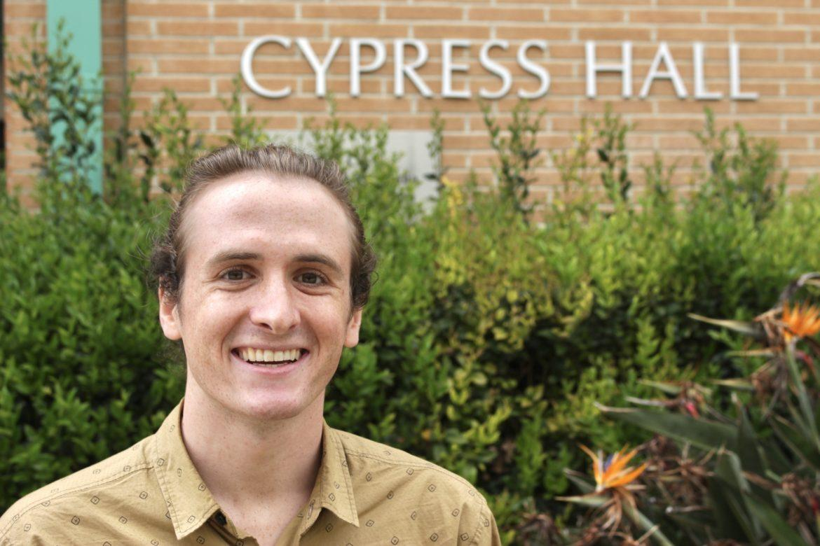 A student in front of Cypress Hall