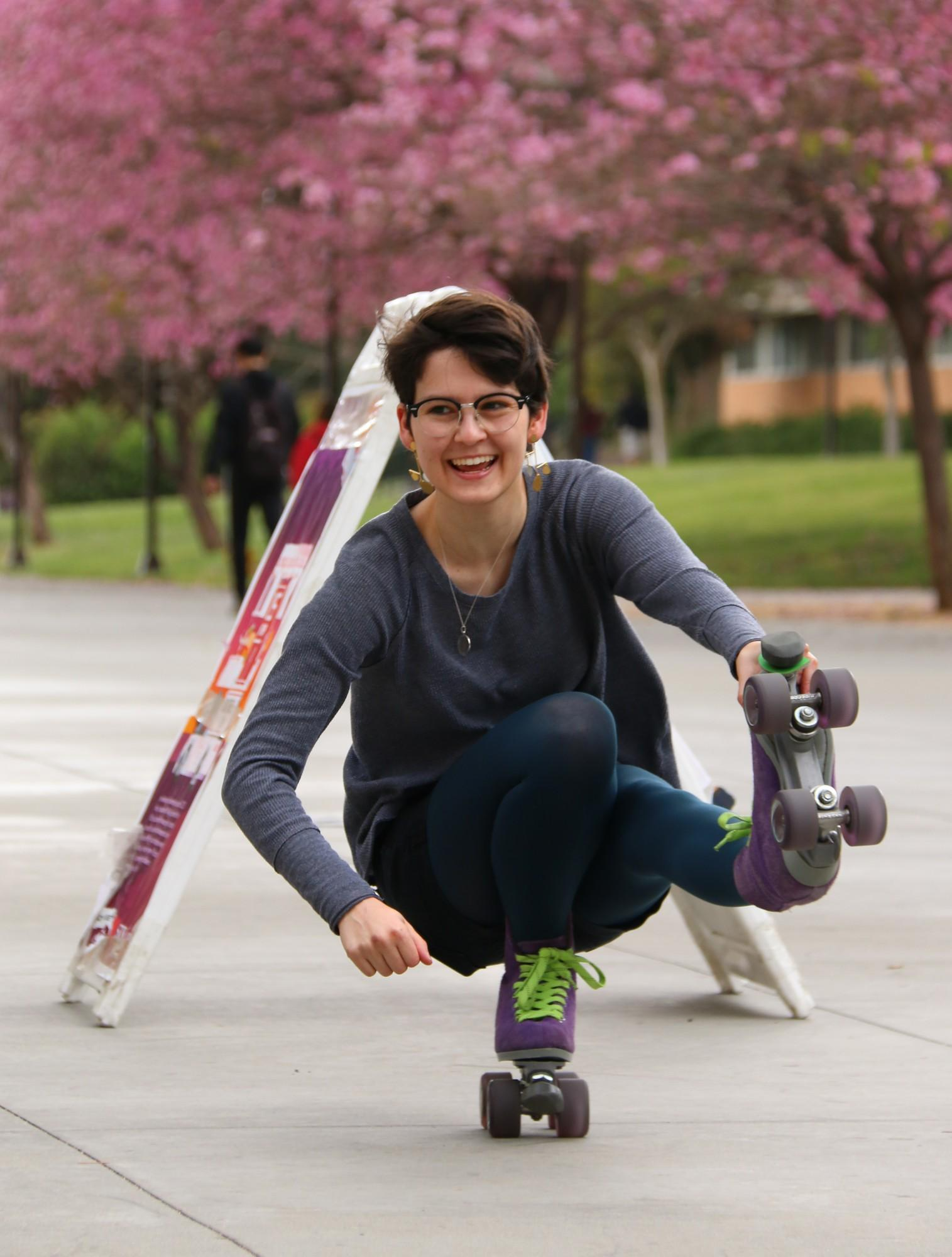 CSUN student, Elinor Shapiro, 21, successfully rolls through an A frame sign on campus while rollerskating in between classes on Tuesday, April 16, 2019. Photo credit: Emmanuelle Roumain