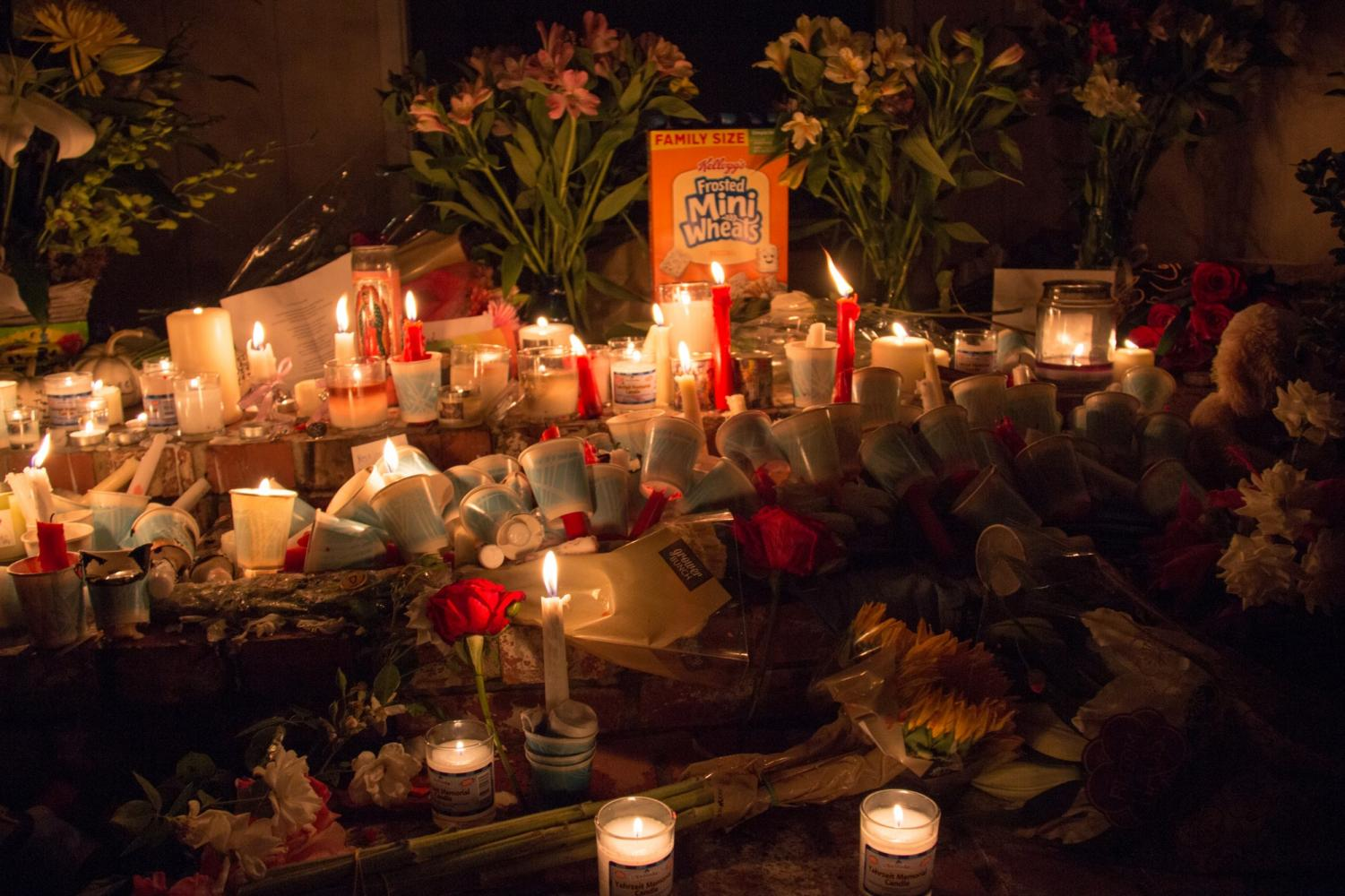 Candles and flowers flood the front steps of the Lertzman home. People gathered outside of the home and left notes, flowers, candles and other personal items. Photo credit: Logan Bik