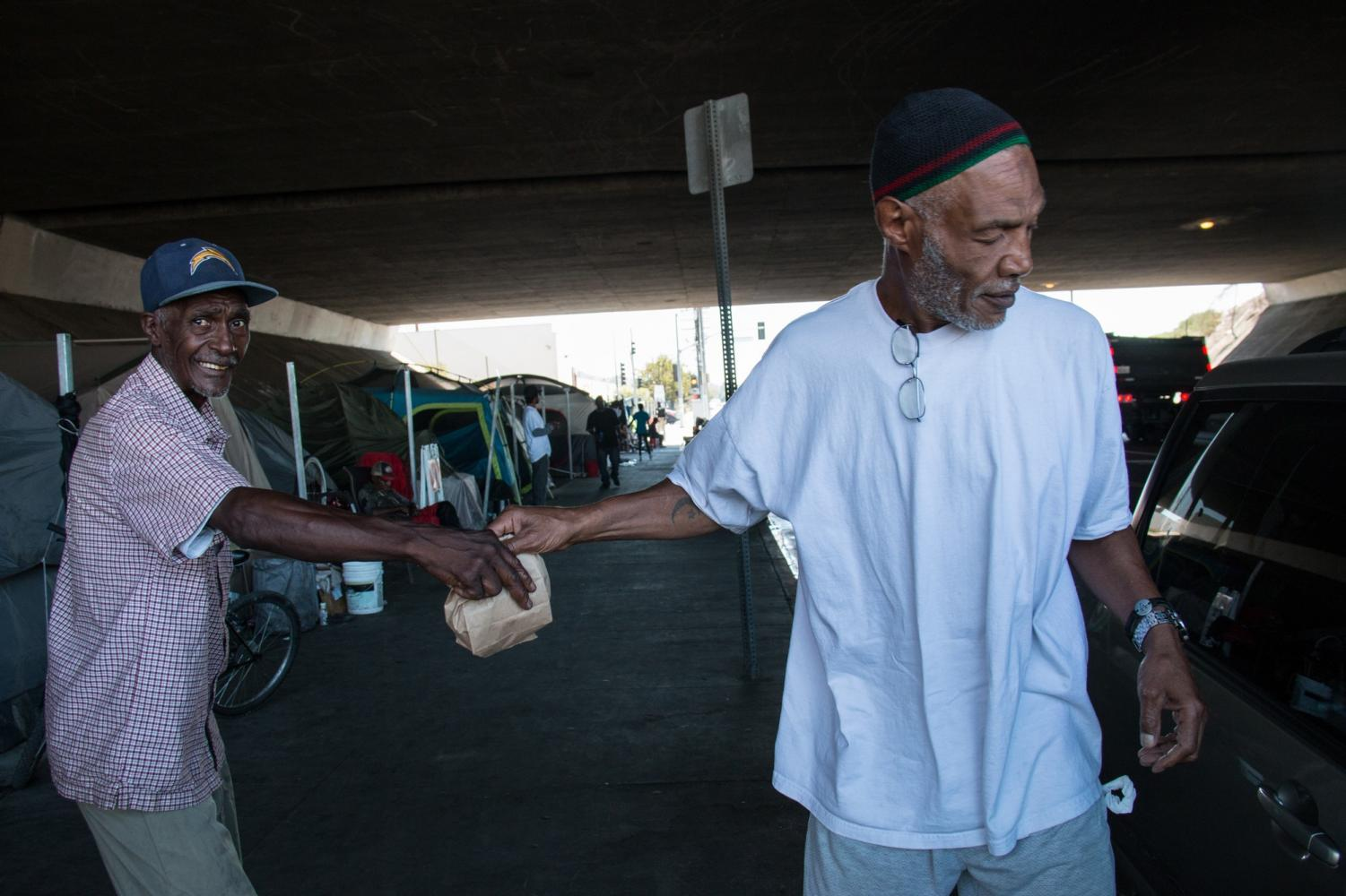 Ali Muhammad, 63, passes a lunch to Duane Pierfax, 62. Pierfax is a homeless man living under a freeway overpass in Pacoima, California. Photo credit: Logan Bik