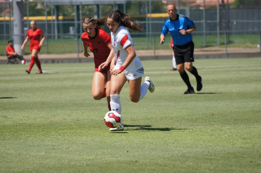 Two female soccer players trying to get the ball