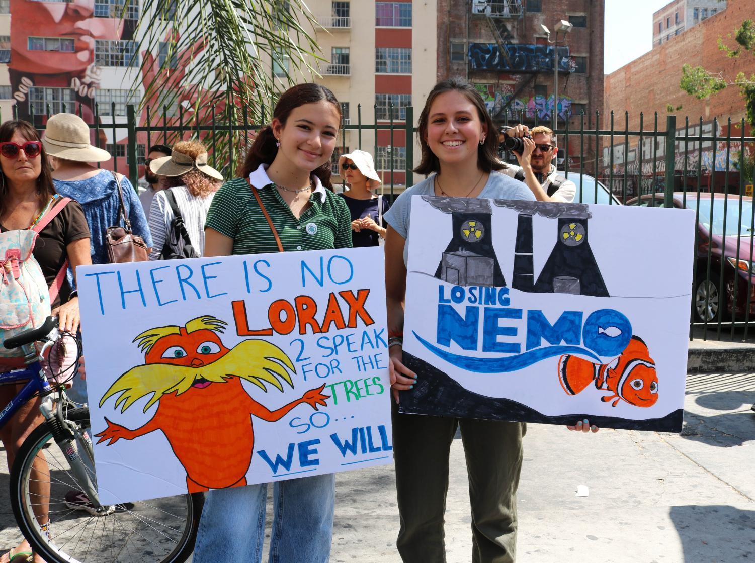 """""""It would be stupid if teachers don't value what's happening in the real world,"""" Madi Kcase said, holding a hand-drawn sign of the Lorax. Her friend, Bianca Richmond, holds a sign showing Nemo from the popular Pixar film as a way to express their support for the Global Climate Strike on Sept. 20 in Downtown LA. Photo credit: Ivan Salinas"""