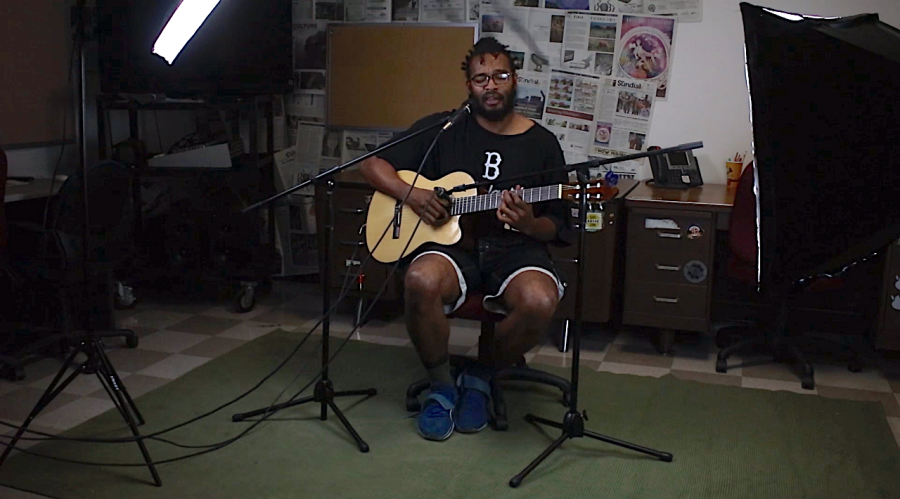 A man playing guitar and singing at the same time