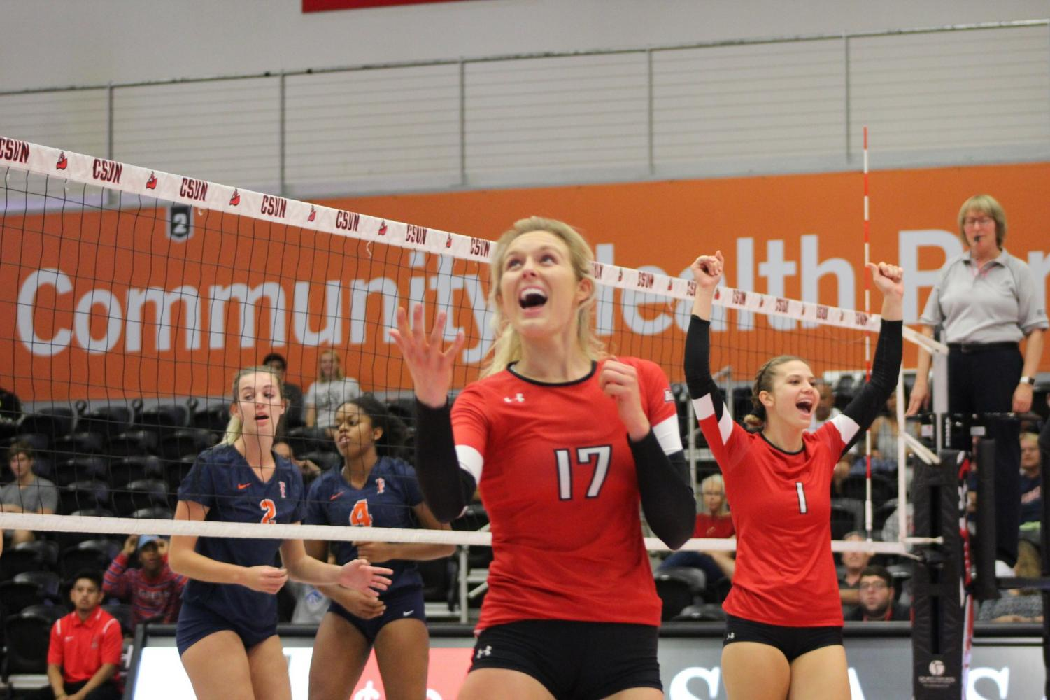 CSUN women's volleyball teammates Lexi McLeod (17) and Taylor Orshoff (1) celebrate a winning shot against Cal State Fullerton on Oct. 20. Photo credit: Charity Wang