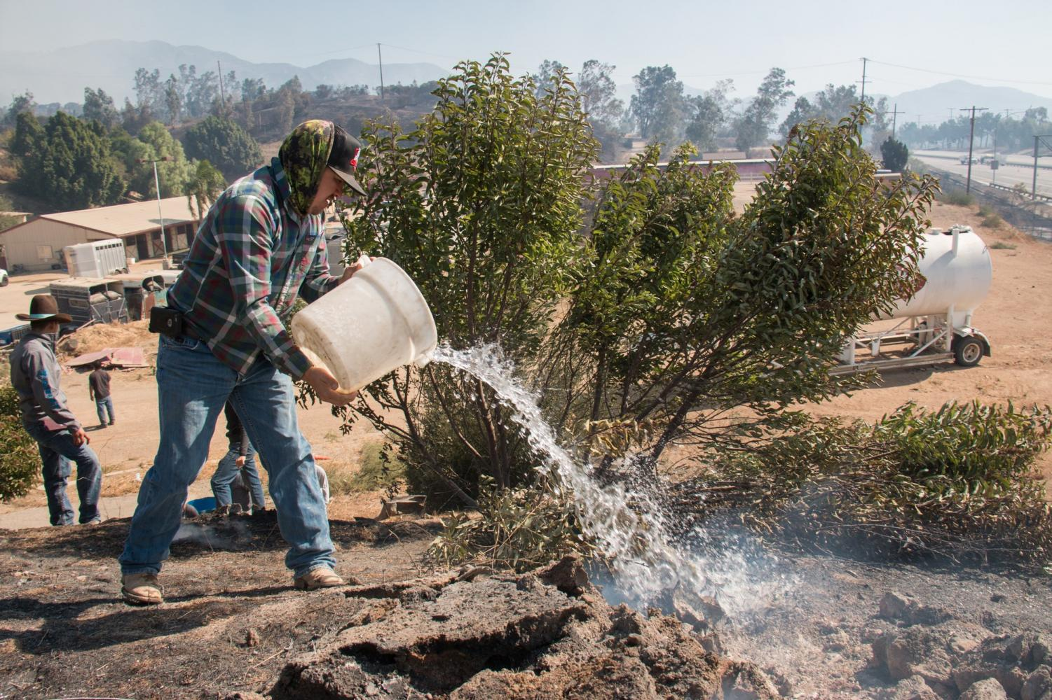 Alejo Morales, 35, pours water onto a smoking truck on the west side of the ranch. The fire was on their property on Thursday, but they were able to fight it off. Photo credit: Logan Bik