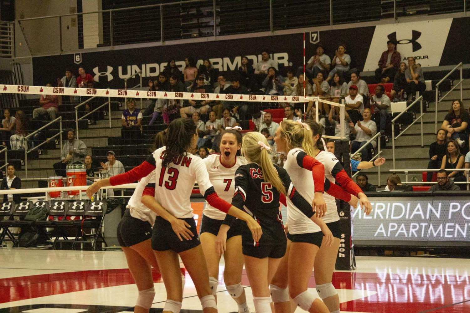 The women's volleyball team celebrates after a point against UC Irvine on Oct. 18. The team won three of the five sets to secure their second home victory of the season. Photo credit: Serena Christie