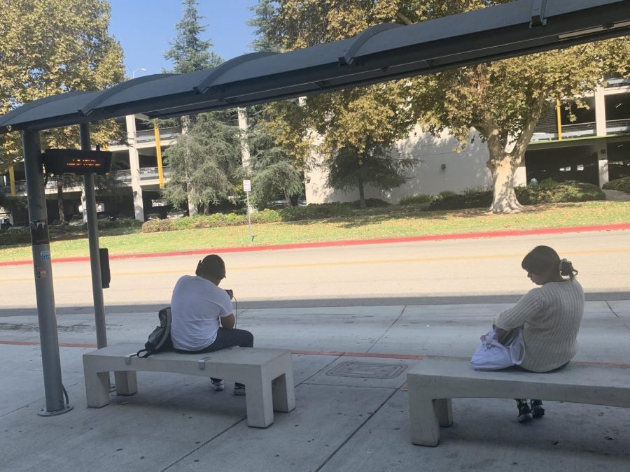 Two students waiting for bus at a bus stop