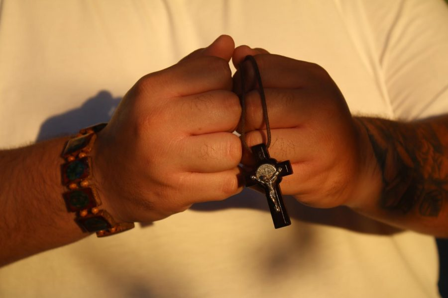 A man holding a cross necklace