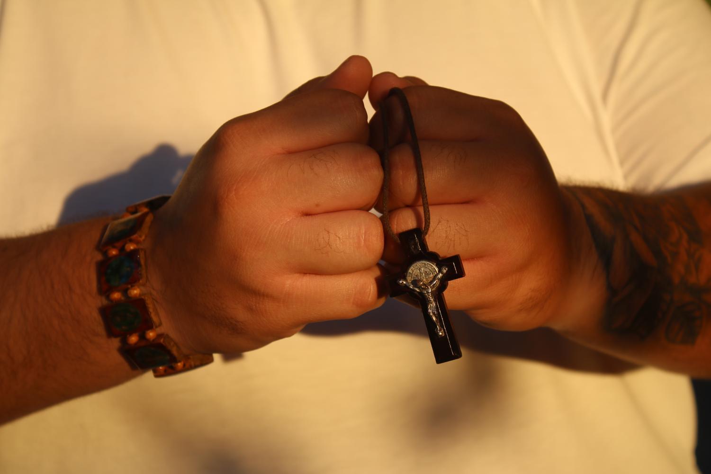 Photo illustration of Andres Soto holding a rosary Photo credit: Logan Bik