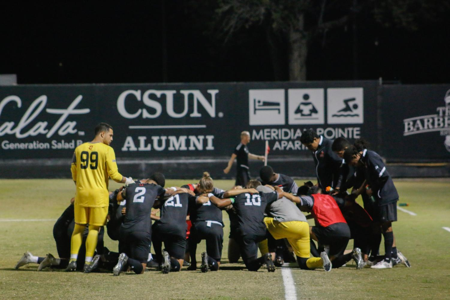 The CSUN men's soccer team huddling after their win on Wednesday, Oct. 16. The team's record moves to 6-6-1. Photo credit: Cesar Saldana