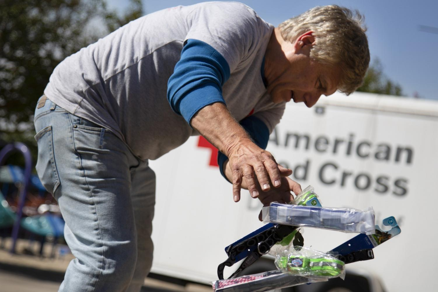 Brad Smulson tosses animal supplies in a bucket, he and his wife think of themselves as the animal Red Cross, they travel to different evacuee centers giving free animal supplies. Granada Hills Rec. Center, Granada Hill, Calif. Oct. 11, 2019. Photo credit: Shae Hammond