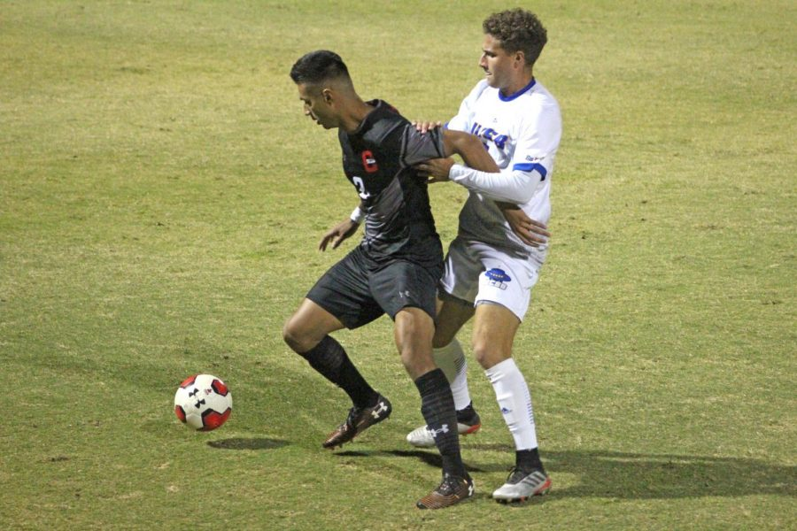 A CSUN Men's Soccer player trying to get pass a defender