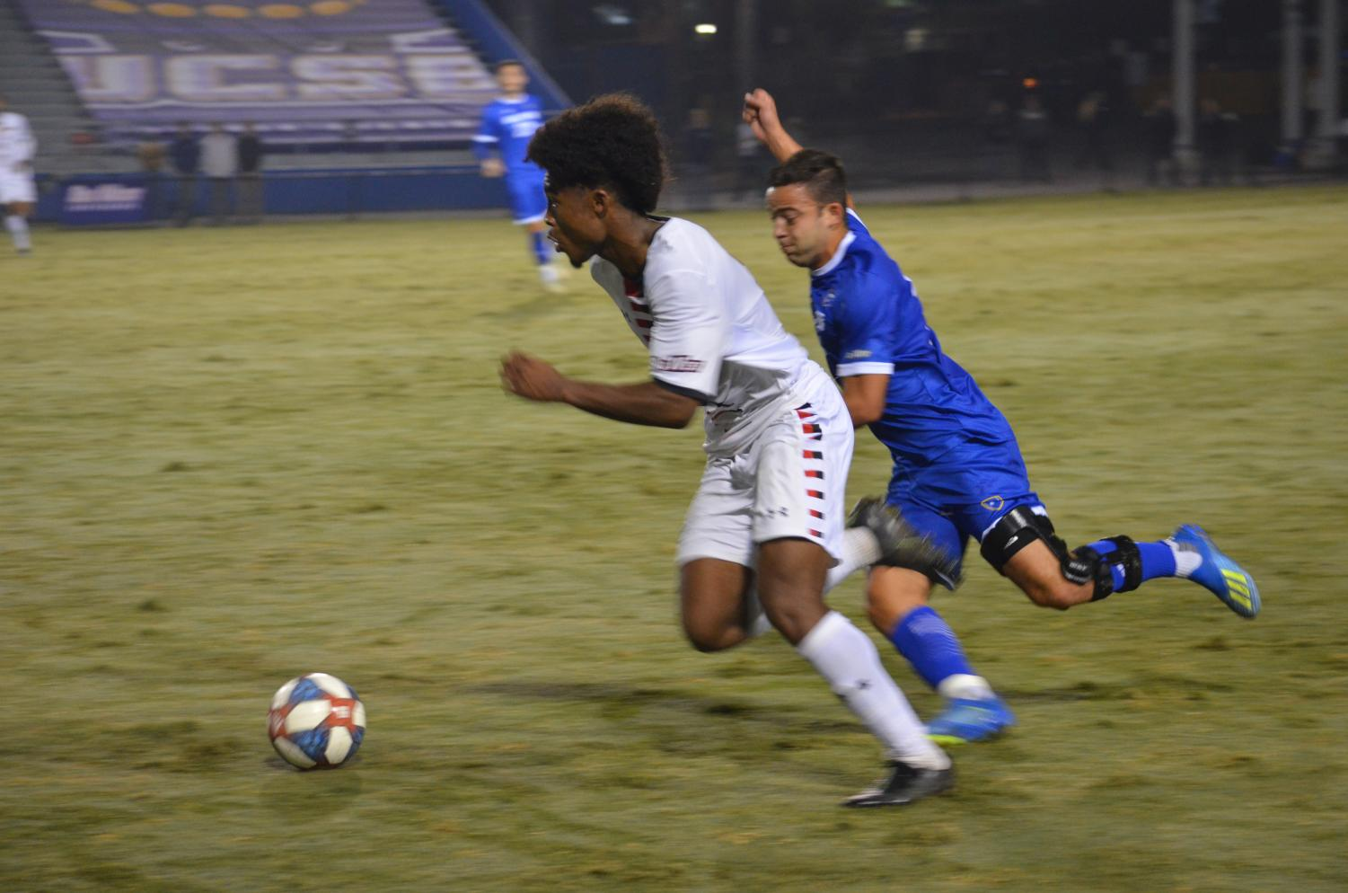 Sophomore midfielder Omar Grey dribbles the ball past a UC Santa Barbra defender during the Big West Tournament Semifinal on Nov. 9. Photo credit: Mano Baghjajian