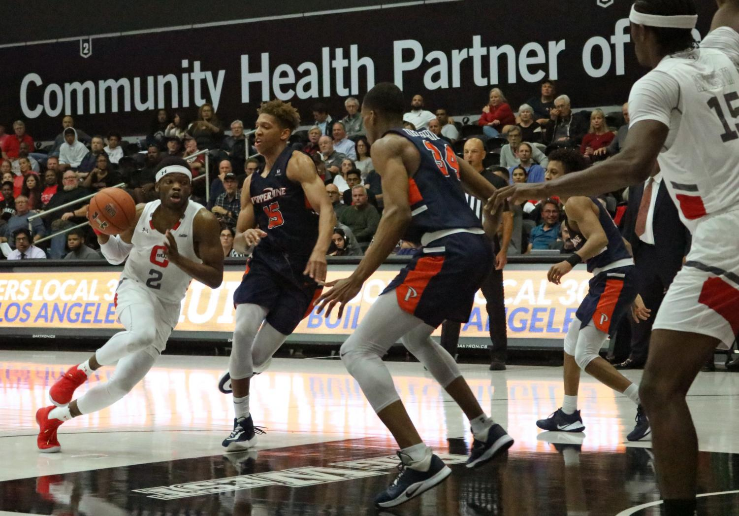 CSUN guard Elijah Harkless (2) dribbles the ball to the key on Nov. 12 in the Matadome. Harkless had six points, ix rebounds and six assists against Pepperdine. Photo credit: Edward Nenedzhyan