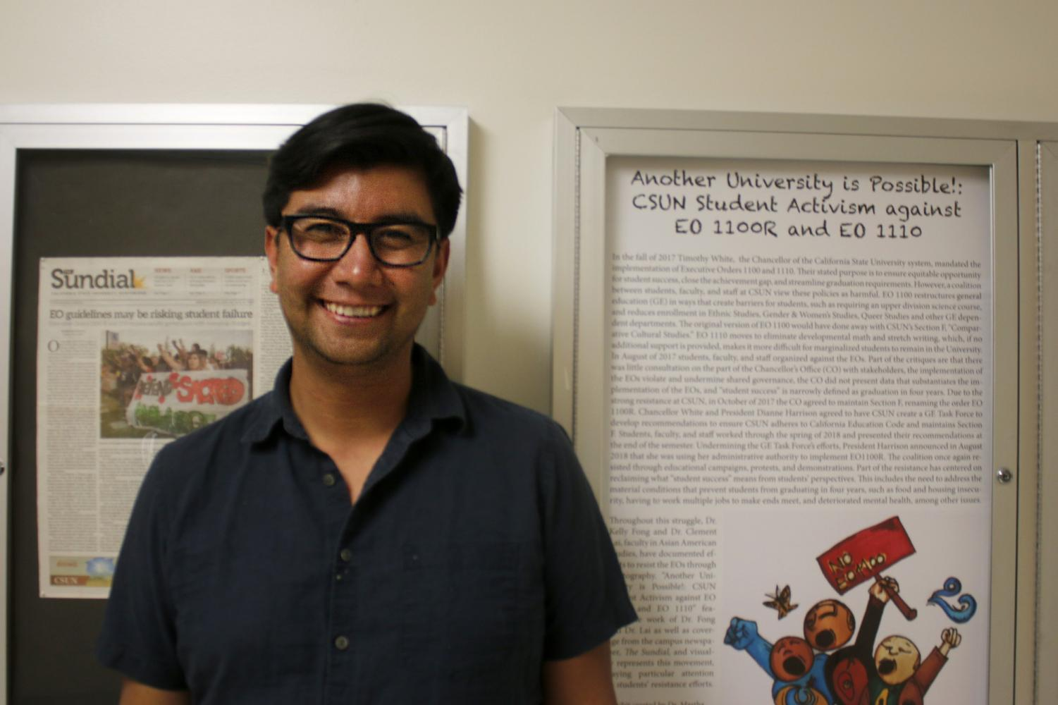 Professor of Chicano/a studies Stevie Ruiz stands next to a poster on student activism for ethnic studies Photo credit: Raychel Stewart