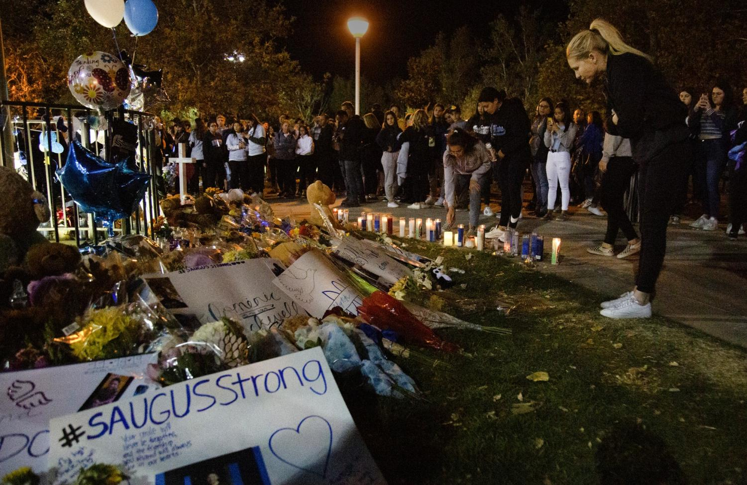 Students gather around the memorial, which circled around the flagpole, on Nov. 17 at Central Park in Saugus to place candles and other memorabilia in support of the community and the deceased after the shooting two days prior. Photo credit: Shae Hammond