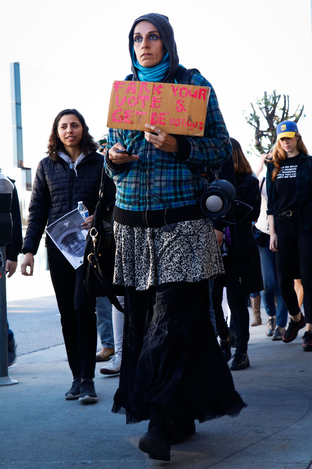 A protester marches up Westwood Blvd playing music. Photo credit: Elaine Sanders