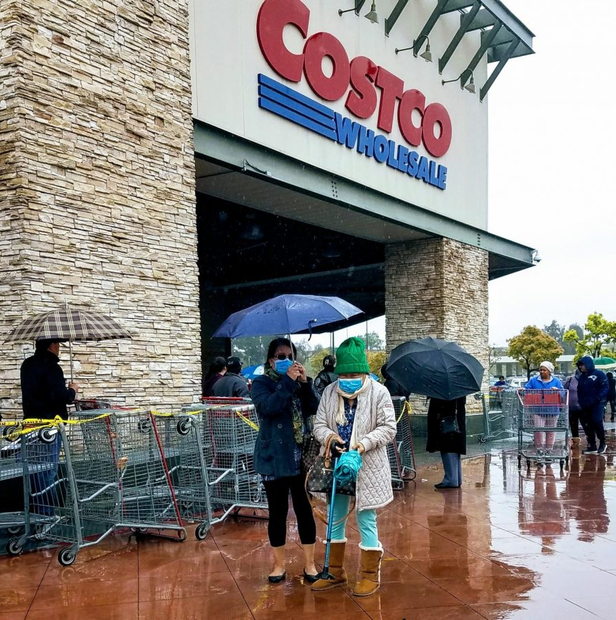 Two customers stand outside of the Costco located on Paxton Street in the San Fernando Valley neighborhood of Pacoima on March 13. Customers had to wait long lines in the rain just to enter the store.