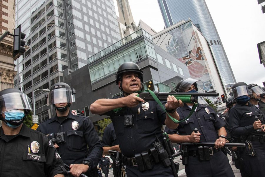 An LAPD officer raises his less-than-lethal weapon as protesters begin throwing debris at police during a protest in downtown Los Angeles on May 29.