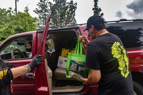 A volunteer loads a bag of resources in a vehicle.